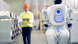 Android and factory worker are meeting and communicating. 4K.