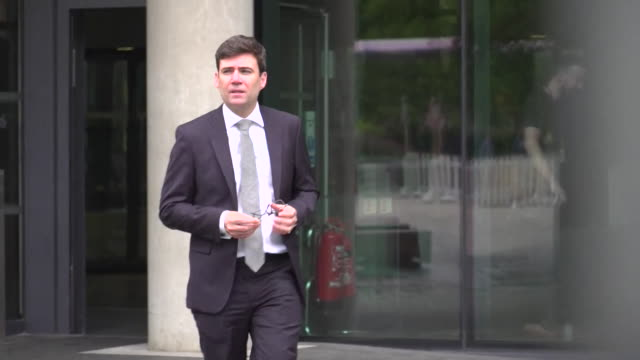 andy burnham, ex-mp and mayor of greater manchester, walks out of a building, july 2017. - rnaウイルス点の映像素材/bロール