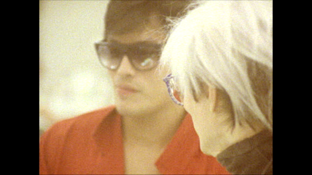 / Andy Warhol and friend Jock Soto talk with woman at the perfume counter of B Dalton department store