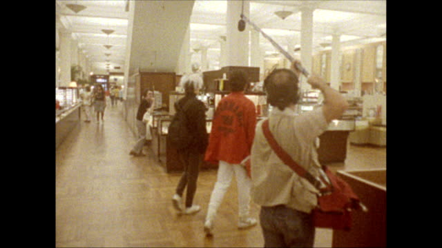 / Andy Warhol and friend Jock Soto walk through B Dalton department store followed by camera crew stop at perfume counter and talk to sales woman