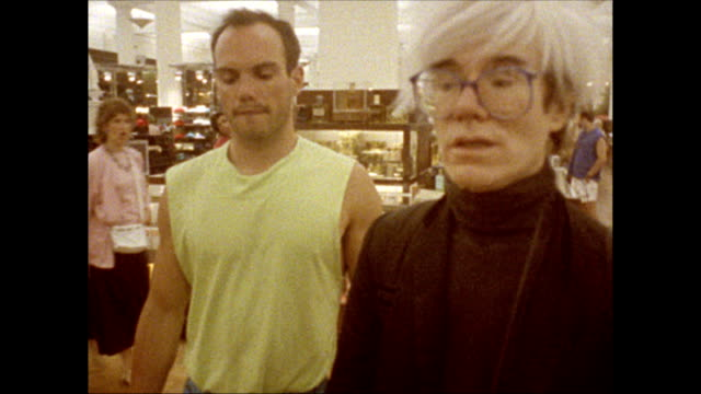 / Andy Warhol and friend take escalator to second floor of B Dalton department store woman comes to greet them
