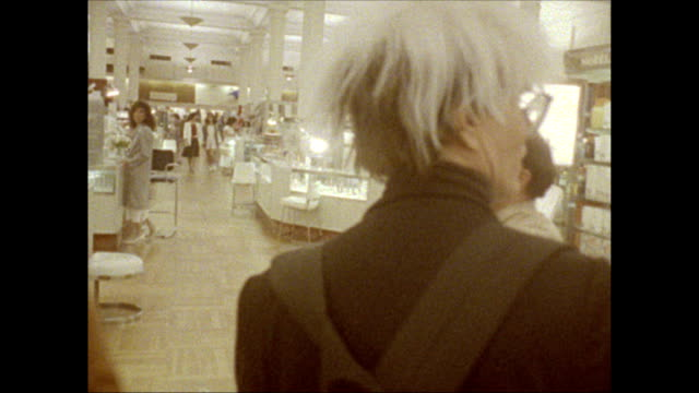 / Andy Warhol and two friends including Jock Soto walk through B Dalton department store
