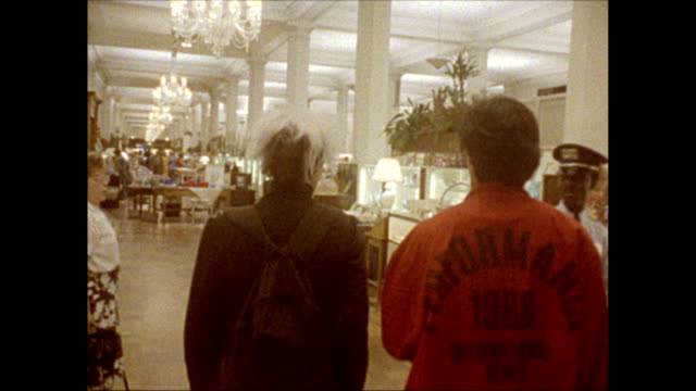 / Andy Warhol enters B Dalton department store with Jock Soto followed by a camera crew