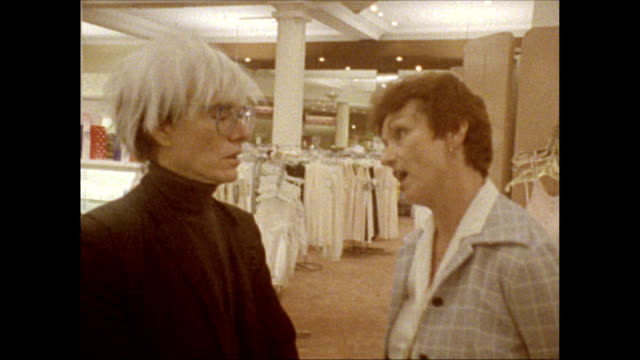 / Andy Warhol speaks with a woman a representative of the B Dalton department store as he strolls around the second floor