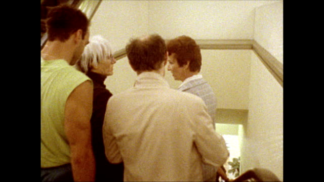 / Andy Warhol takes the escalator down the the first floor accompanied by a friend and a store representative