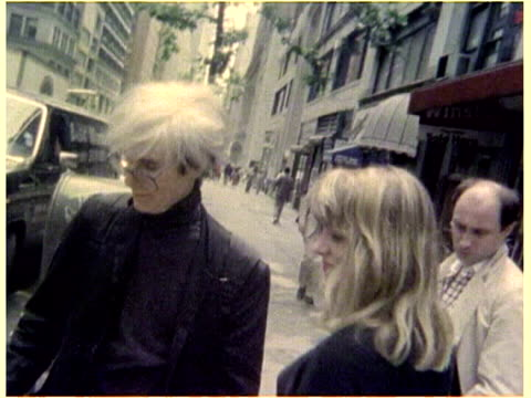 Andy Warhol walking a dog a pug in midtown accompanied by a young woman and Russ Karel Andy Warhol in Midtown on January 01 1986 in New York NY
