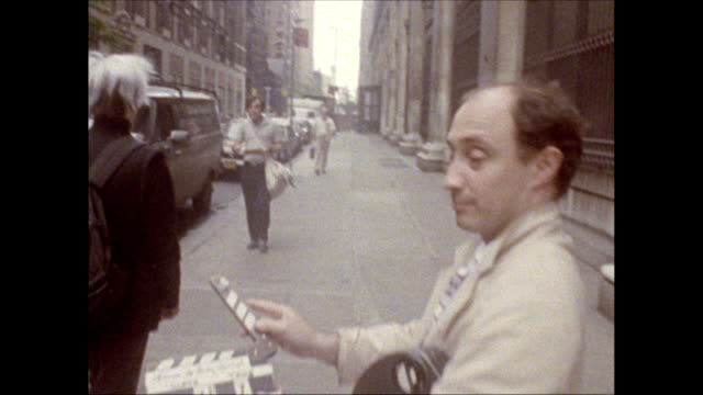 / Andy Warhol walking along 35th St with friend and camera crew signs autograph for man