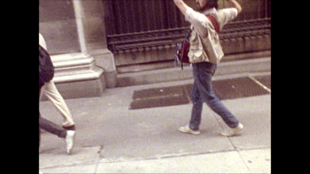/ Andy Warhol walking along East 35th street with a friend followed by camera crew