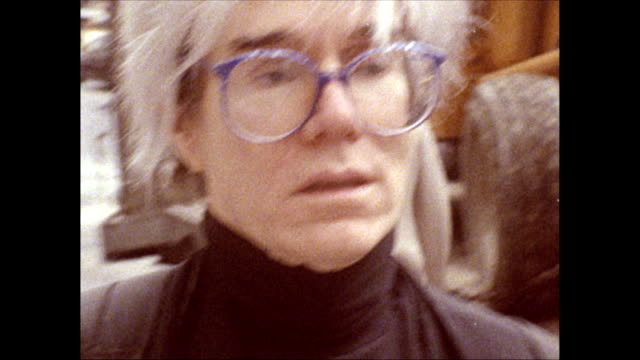 / andy warhol walks along 42nd street crowded with people, past shops, neon signs advertising peep shows and other erotica, porn and martial arts... - street name sign stock-videos und b-roll-filmmaterial