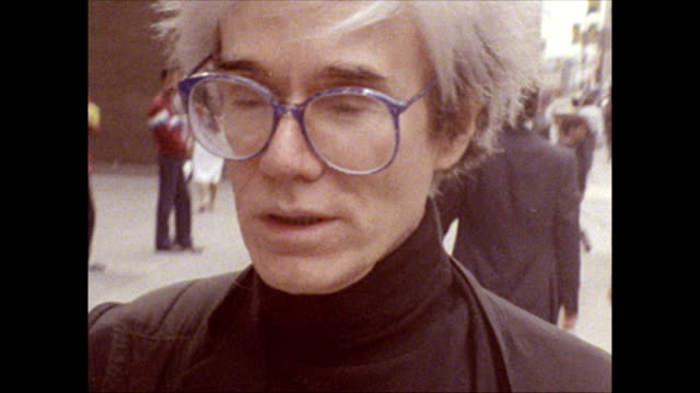 / Andy Warhol walks along 42nd street crowded with people past shops neon signs advertising peep shows and other erotica porn and martial arts...