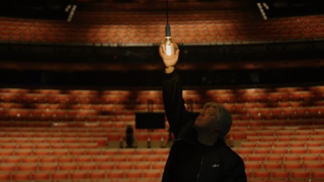 "ange sullivan, head of lighting checks on the ""ghost light"" hanging on the stage of the joan sutherland theatre at the sydney opera house on may 03,... - オペラ座点の映像素材/bロール"