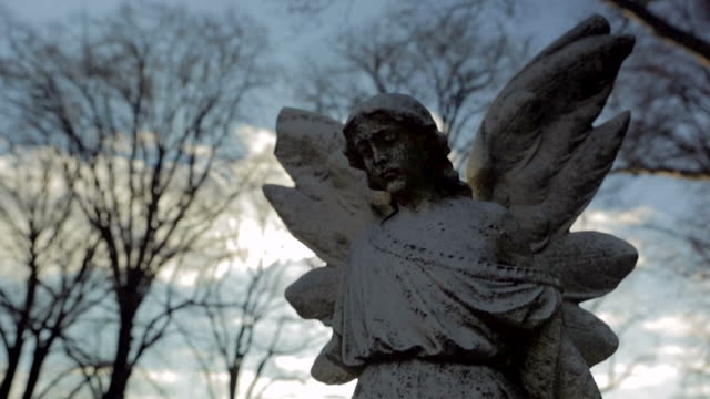 vídeos de stock, filmes e b-roll de estátua do anjo ao pôr do sol, com bela sol refração câmera lenta - estátua