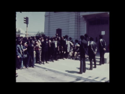 angela davis trial; usa: california: los angeles: st. augustine's church: int flashback: funeral of soledad brothers, killed in shoot-out after... - 敬礼点の映像素材/bロール