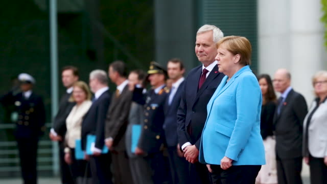 angela merkel is seen shaking alongside finnish prime minister antti rinne during the german national anthem - shaking stock-videos und b-roll-filmmaterial