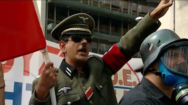 angela merkel visit / protests on streets greek protester dressed in nazi uniform chanting on street sot - vox populi stock videos & royalty-free footage