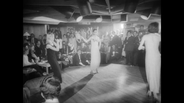 vídeos de stock, filmes e b-roll de angela of london designer reveals spring collection in manchester / 45 record spinning on player / models dancing in middle of room with audience and... - 1965