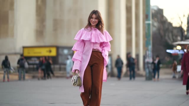 angelica ardasheva wears a pink ruffled long shirt a bag with embroidery brown flared pants pink shoes outside rochas during paris fashion week... - pink shirt stock videos and b-roll footage