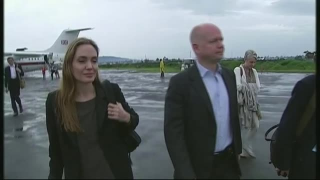 Angelina Jolie files for divorce from Brad Pitt LIB Goma EXT William Hague and Jolie along at airport INT Women patients singing and clapping in...