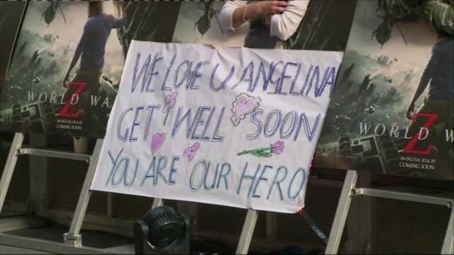 Angelina Jolie has ovaries and fallopian tubes removed R02061306 / London 'We love u Angelina get well soon you are our hero' poster in crowd at...