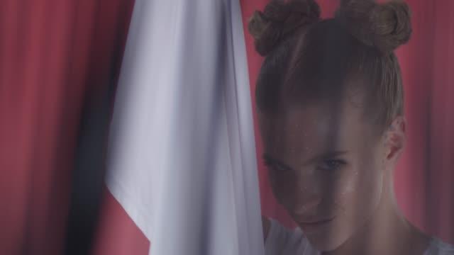 angel-like fashion model shows facial expressions, hiding beneath white sheet. fashion video. - eyelash stock videos & royalty-free footage