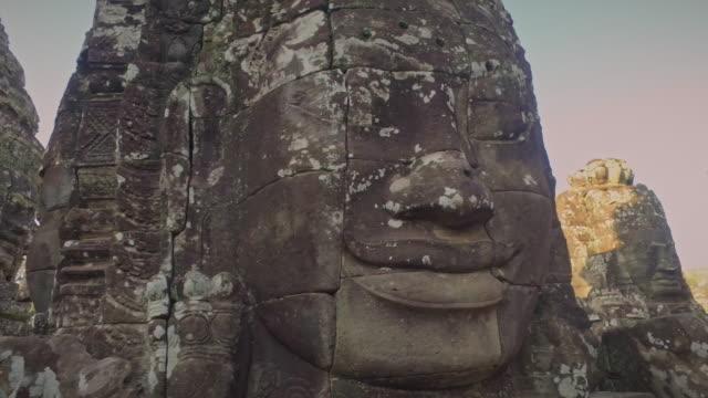 angkhor wat kambodscha angkor thom stein gesichter 4k video pan shot - basrelief stock-videos und b-roll-filmmaterial