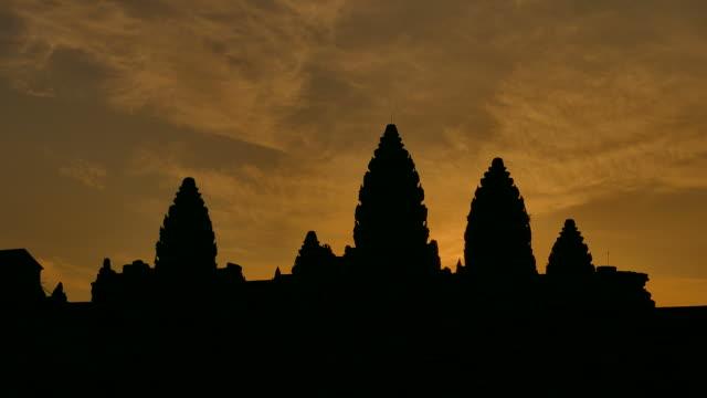 vídeos de stock e filmes b-roll de templo de angkor wat, camboja nascer do sol silhueta - circa 13th century