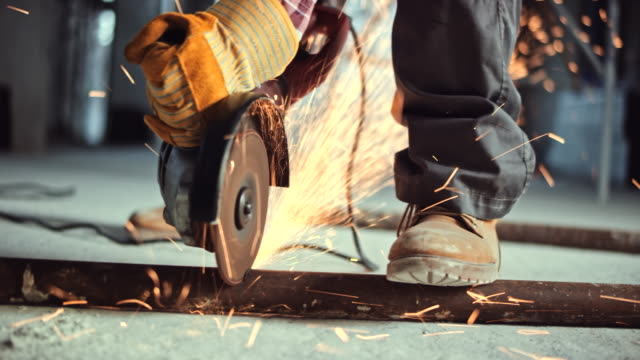 angle grinder being used to cut through a metal pipe on the floor at the construction site - metal stock videos & royalty-free footage