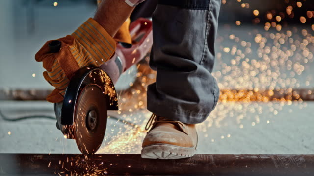 slo mo angle grinder causing sparks when cutting through metal pipe - construction worker stock videos & royalty-free footage
