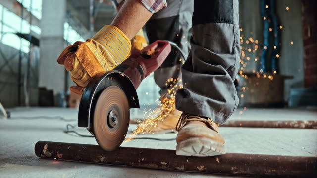 slo mo ld angle grinder causing sparks while being used to cut metal - construction worker stock videos and b-roll footage