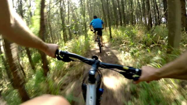 POV angle of man mountain biking through tropical forest