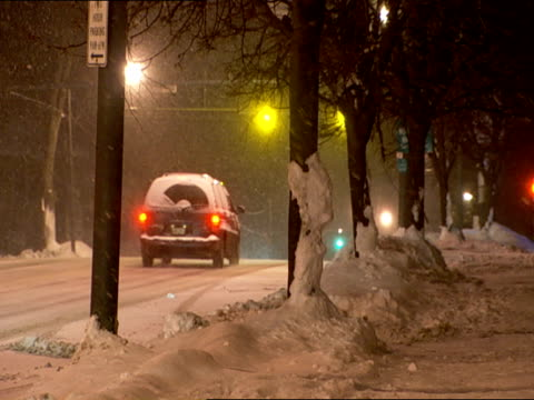 vidéos et rushes de angle on light traffic on small town cleared road lined w/ trees & sidewalk, cars, truck stopping at red traffic light, snow falling, snowing. - phare de véhicule