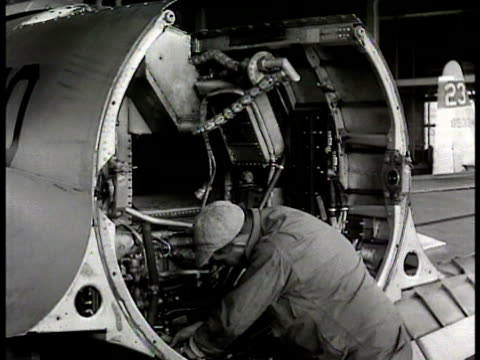 vídeos de stock, filmes e b-roll de angle on ws maintenance hangar mechanic w/ jet engine mechanic working on jet engine over hauling mechanics putting engine back together crew members... - 1948