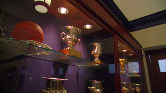 Angle On TD WS Tall wooden brass NCAA trophies under glass in display case