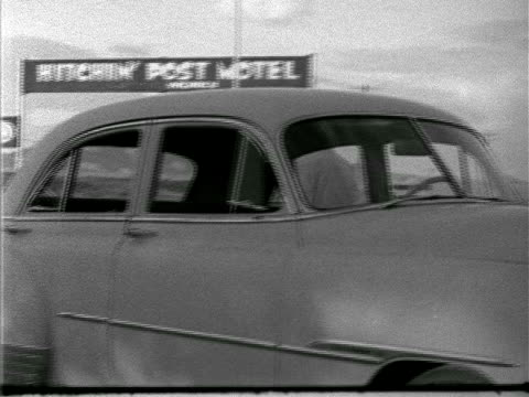 motel angled ws 1951 chevrolet belair sedan w/ young male teenager amp adult male getting out of car 'hitchin' post motel' tall roadside sign bg male... - sedan stock videos & royalty-free footage