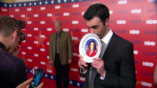 HD Angled MS Actor Reid Scott on red carpet posing with Selina Meyer commemorative plate correspondent Bob Simon