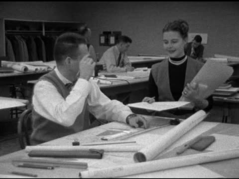angled adult male architect, draftsman dressed in sweater vest & bow tie sitting at drafting table using slide rule , woman walking up handing him... - slide rule stock videos & royalty-free footage