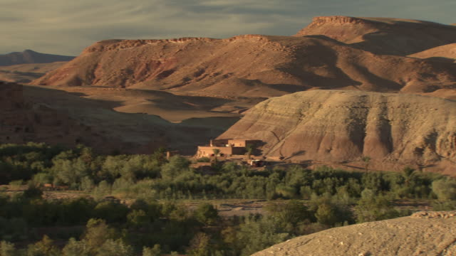 Angled WS Atlas Mountains southern foothills w/ structure at base of small mountain REVERSE PAN Landscape XWS Fortified clay brick city w/ defensive...