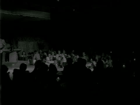 angled ws audience partially lit from stage lights sitting at tables applauding other people in silhouette fg show room clapping appreciation - 1952 stock videos and b-roll footage