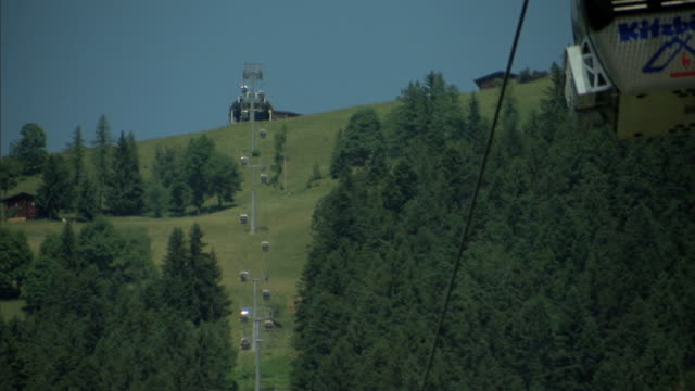 angled austrian alps cable car gondolas moving on cables in opposite directions out of frame, tree covered mountain bg. excursion, sightseeing,... - 北チロル点の映像素材/bロール