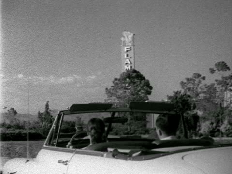 angled ws couple in convertible car driving by the flamingo hotel building amp parking lot marquee 'spike jones' ad gambling gaming 'the strip' - 1952 stock videos and b-roll footage