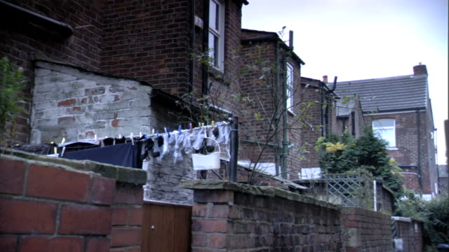 angled ws back of older brick row houses terrace housing w/ laundry hanging on clothesline behind short wall brick fence enclosed yard fg - terraced house stock videos & royalty-free footage