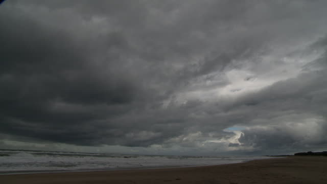 Angled WS Beach RAPID MOTION Indian Ocean waves breaking on beach heavy dark gray cumulonimbus storm clouds moving across sky