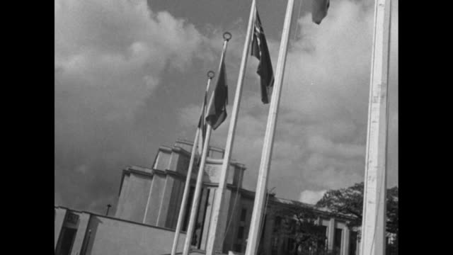 angled beauty shot eiffel tower in background with row of flags of un nations on pole in front / vs ext palais de chaillot with flags statue / shaky... - ex unione sovietica video stock e b–roll