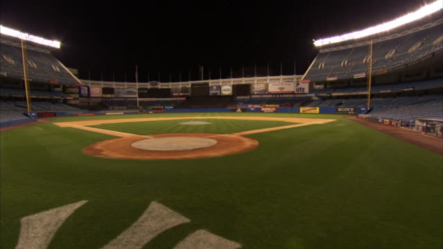vídeos y material grabado en eventos de stock de angled ws empty old yankee stadium angled dolly back from field crane down behind ny logo on grass behind base - base home