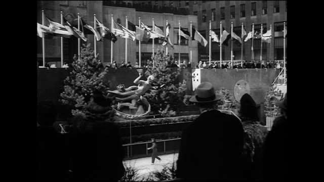 vídeos de stock, filmes e b-roll de hd angled ws gilded statue of prometheus above sunken central plaza ice rink w/ people skating people standing edge of wall united nations members... - pista de patinação no gelo