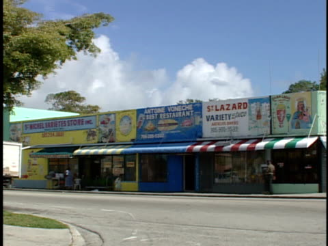 *angled ws brightly colored strip mall shops along sidewalk few unidentifiable people variety store restaurant pan zi ws st gerard botanica store w/... - haiti stock-videos und b-roll-filmmaterial