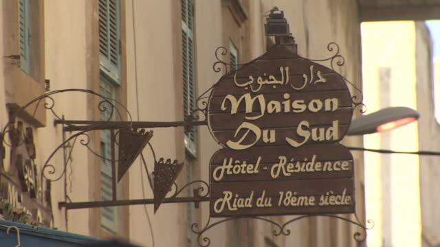 TU Angled WS Brown Maison Du Sud HotelResidence bilingual sign extending from shaded building w/ contrasting color shutters