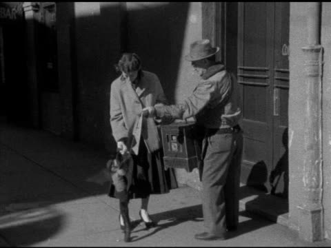 angled ws brunette female standing on sidewalk holding dressed capuchin monkey on arm holding out change in hand organ grinder giving tug on chain... - street performer stock videos & royalty-free footage