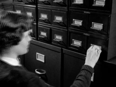 Angled MS Card catalog files stacked on top of rows of file cabinets young adult female opening card file taking out batch of handwritten index cards...