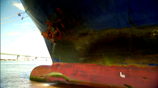 Angled WS Cargo ship side w/ raised anchor water pouring out from behind Rust rusted corrosion stained docked